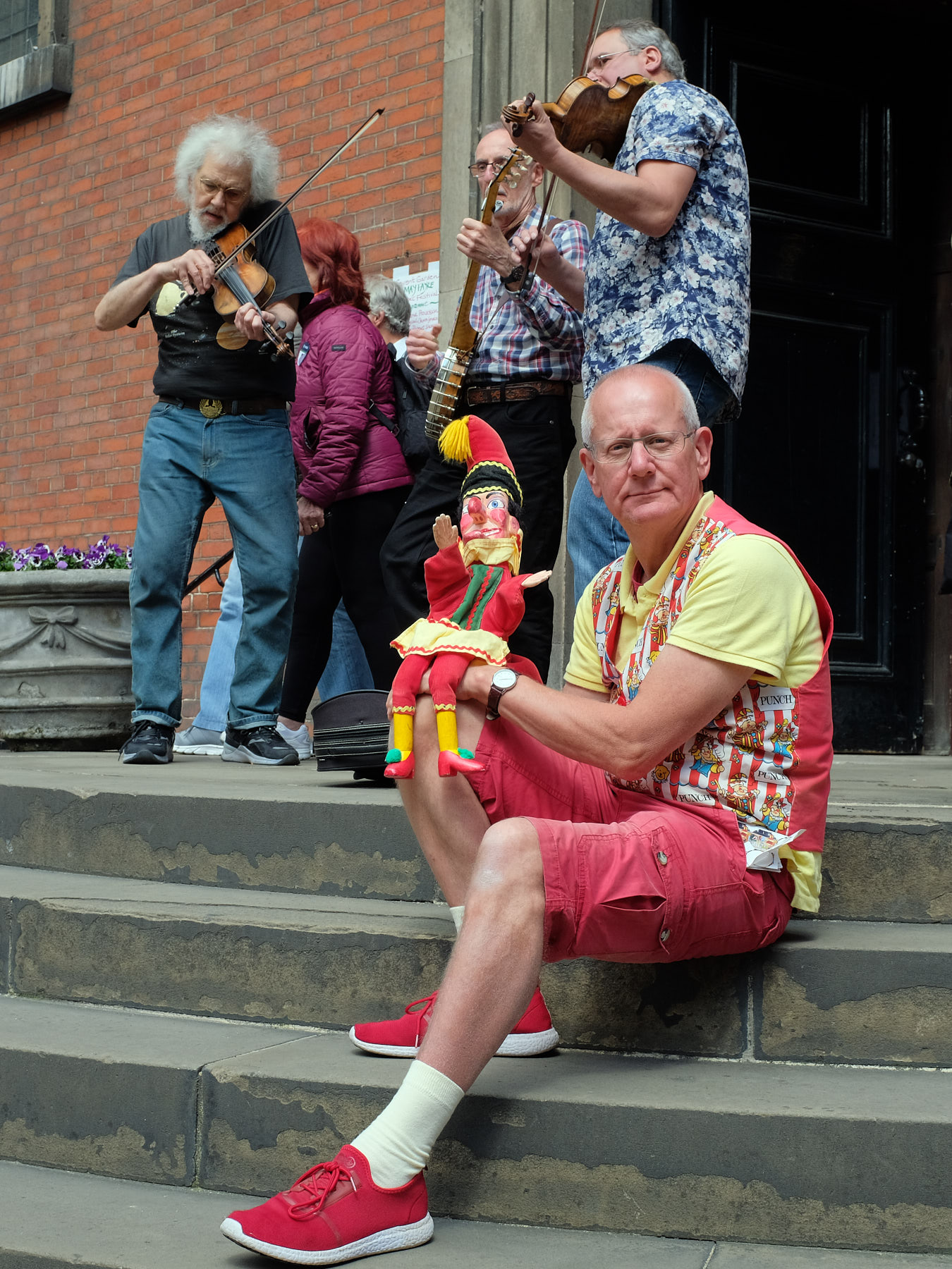 A puppeteer poses with Mr. Punch while The Lost Marbles string band shred behind him.