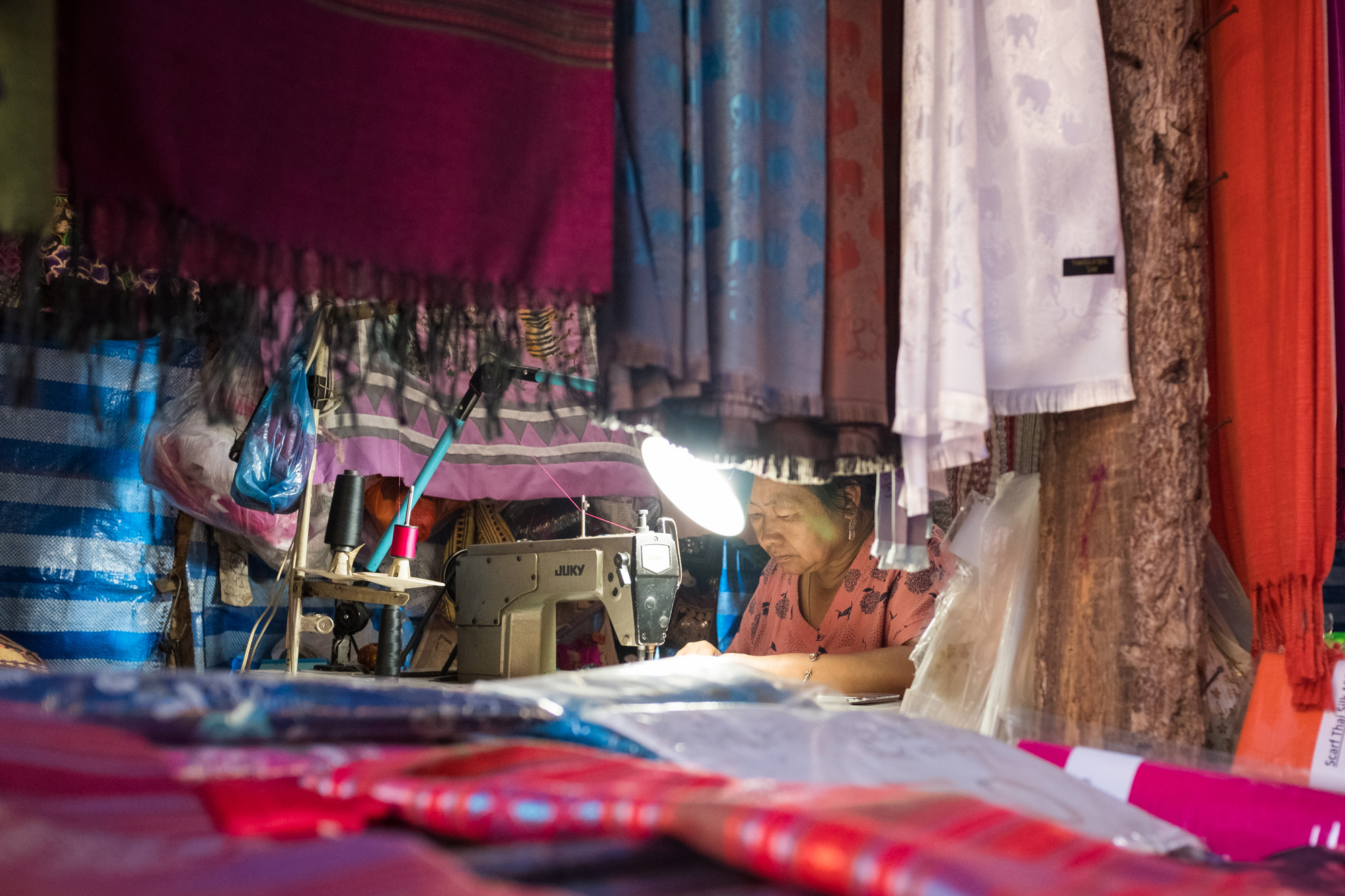 The Seamstress   Hidden deep within the fabrics and textures she sewed away patiently. Surrounding her was a seemingly endless pile of garments ready for the tourists trade.   - Doi Pui Village, Chaing Mai, Thailand