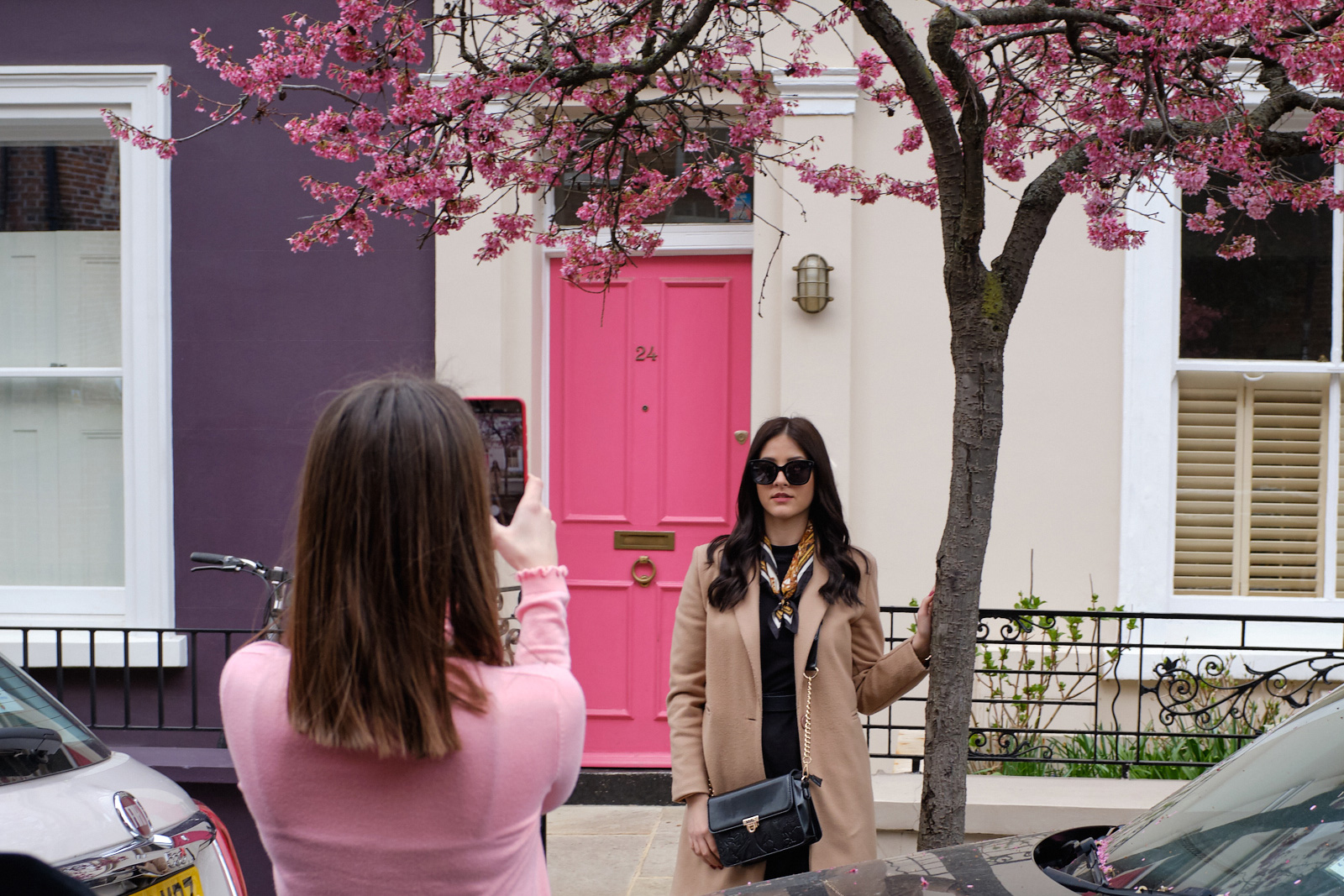 Probably Influencing   The story is that the residents of Notting Hill have a problem with influencers continually harassing them by taking photographs outside of their homes. I'd encourage shark infested moats.