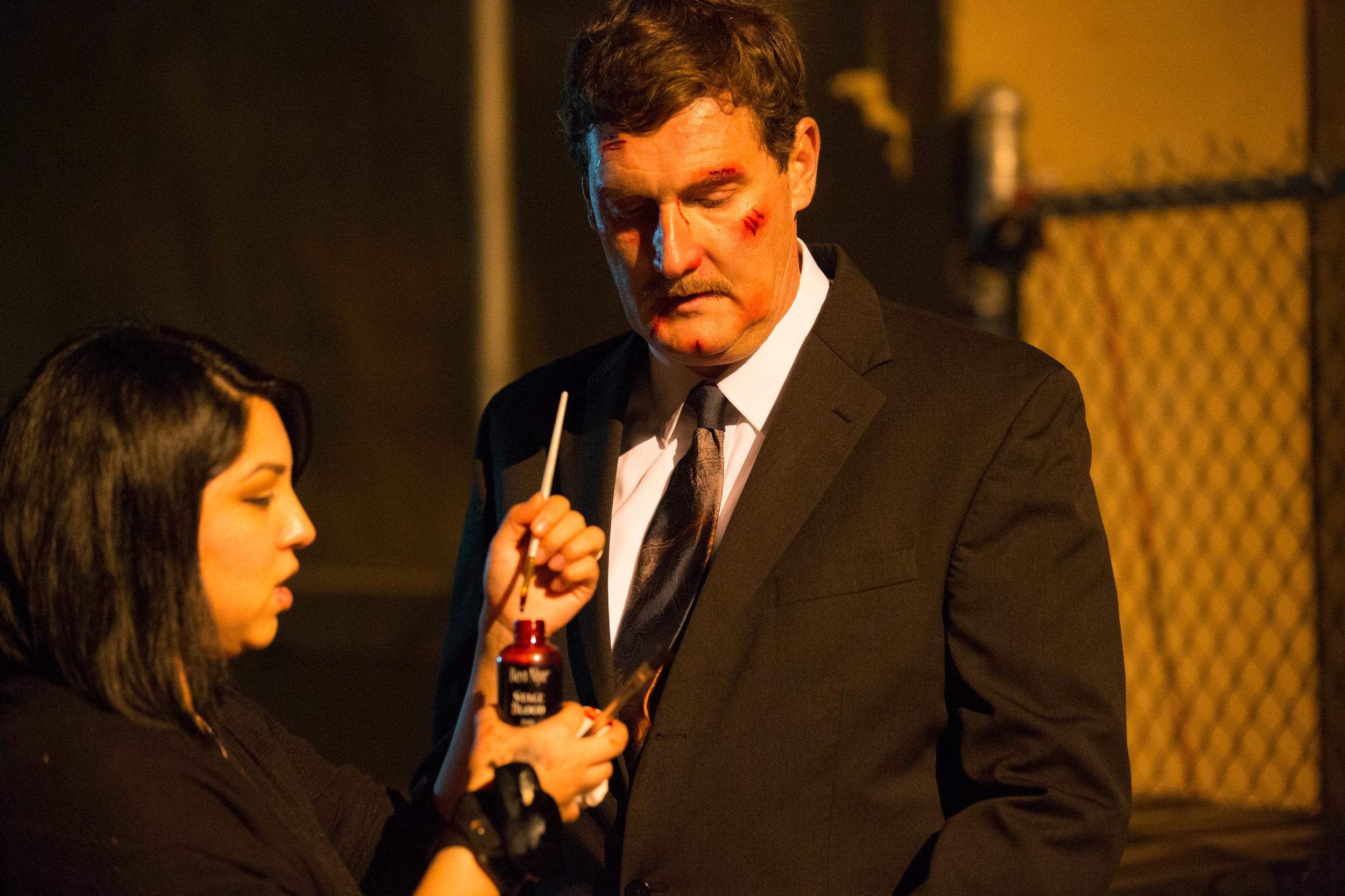 Amber Medina touches up Steve Hrdlicka's (Businessman) makeup. Photo by PJ Barlow.