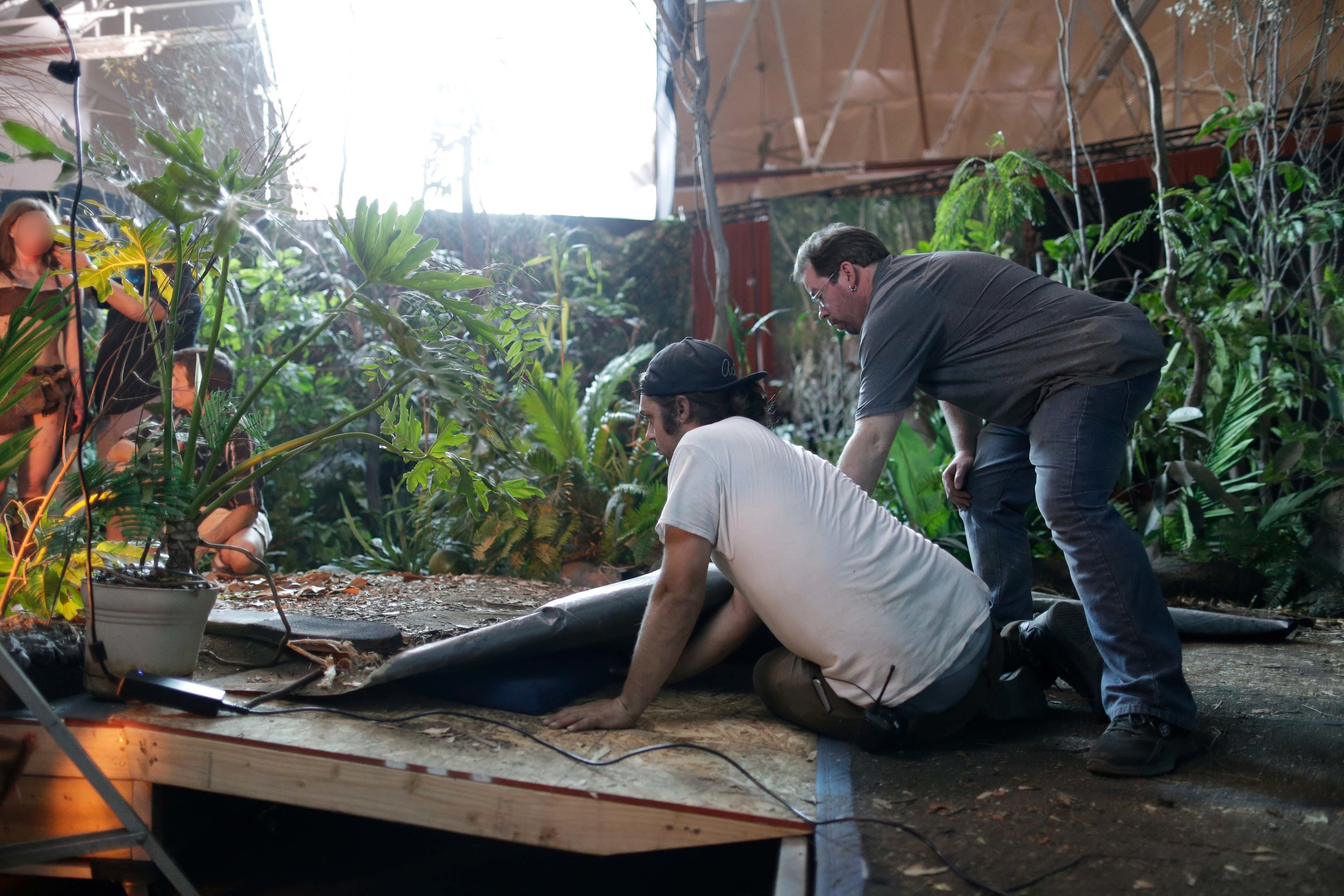 Set Designer Max Martinez and Assistant Set Designer Jason Moore laying down the floor on their studio jungle. Giant mosquitoes not included.