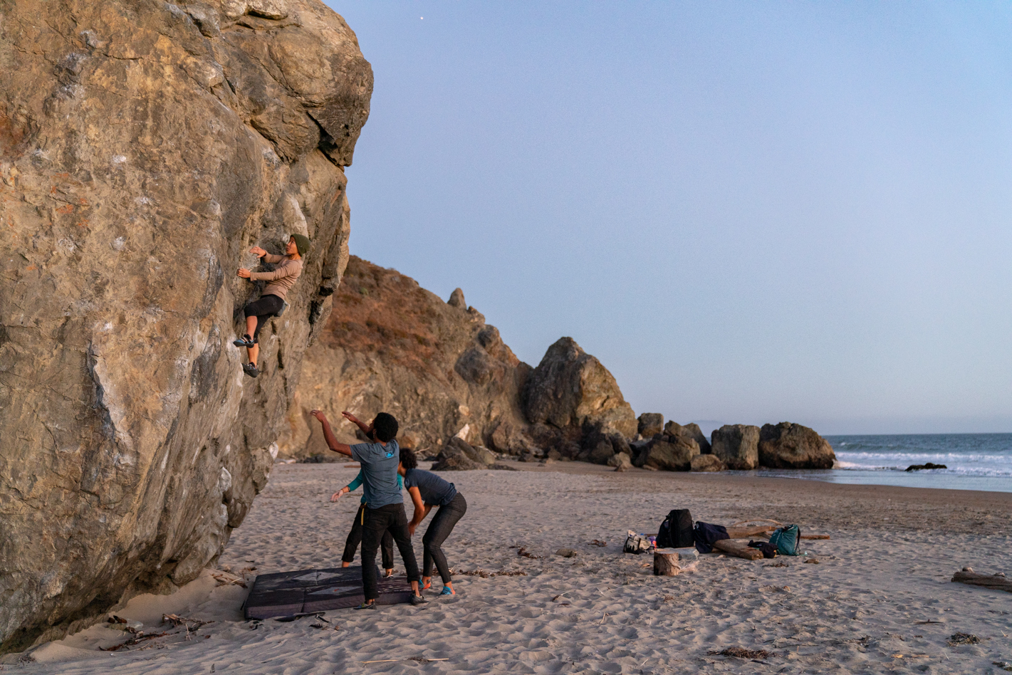A group of climbers (Narinda H., Kaily H., Justin F.P. and Jael B.) take on some sunset bouldering at Stinson Beach, CA.