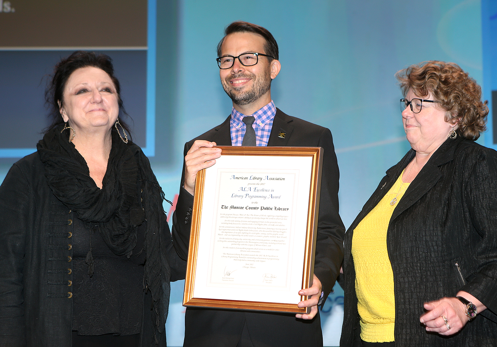 ALA President Julie Todaro (left) and Cultural Communites Chair Cassandra Barnet present Michael Hoerger of Monroe County Public Library the ALA Excellence in Library Programming Award on Sunday, June 25, in Chicago. (Photo by American Library Association)