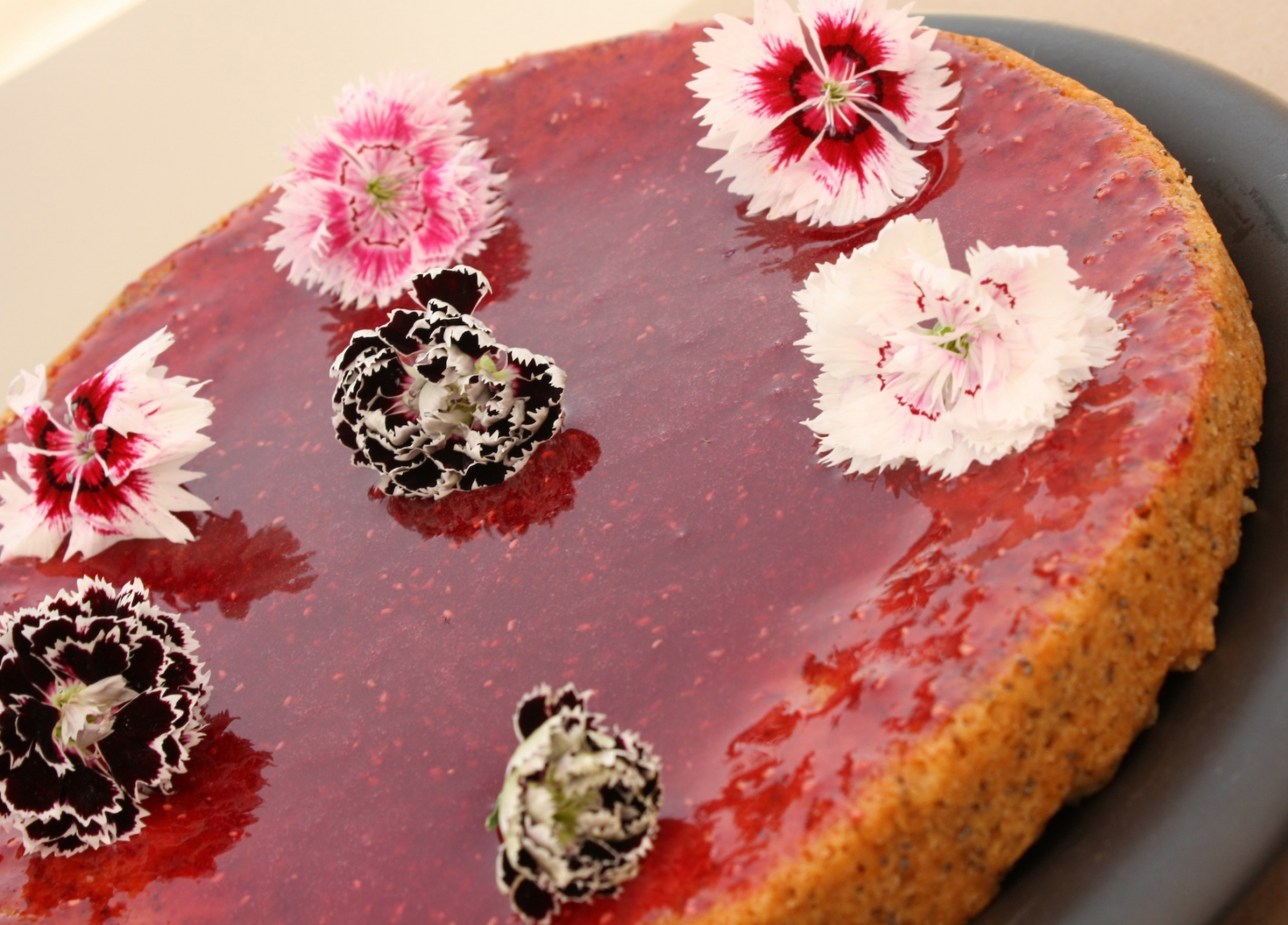 An orange-poppy seed cake, resplendent with a berry glaze and scattered with fresh edible dianthus blooms, which would make a very fitting Birthday Cake for a person born in January. ( vegan recipe )