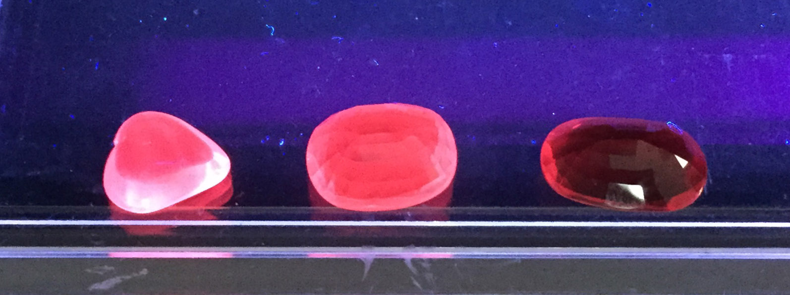"Fig. 1: (from left to right):  Burmese ""Pigeon's Blood"" ruby  (very strong fluorescence),  Mozambican ruby type I, ""Pigeon's Blood""  (strong fluorescence),  Mozambican ruby type II , (weak fluorescence)   COPYRIGHT © 2015 BY GRS GEMRESEARCH SWISSLAB AG"