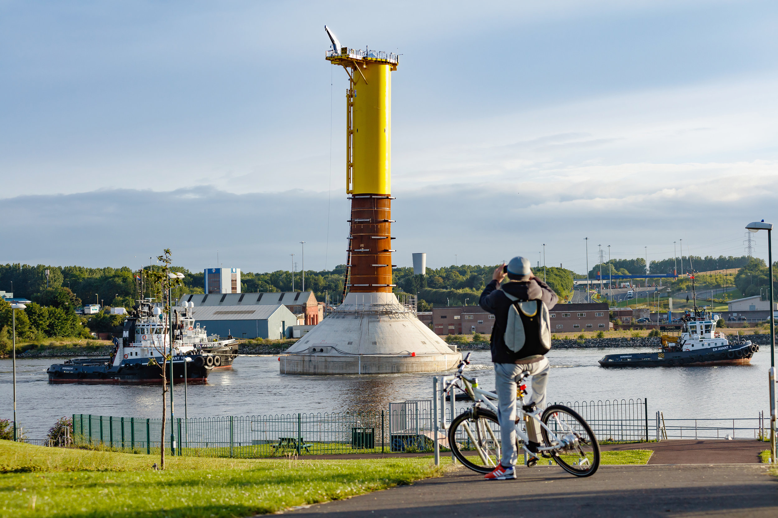 Wind farm gravity base floating down the river Tyne, watched by an onlooker on an electric bycycle.