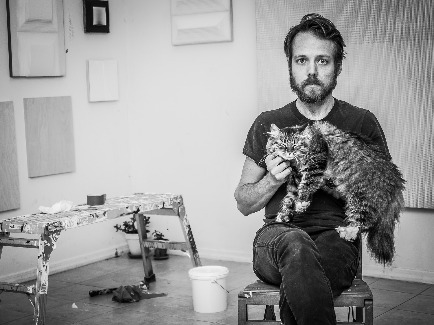 Portrait of Artist Mitchell Wright holding his cat in Art Studio Greenpoint Brooklyn NYC