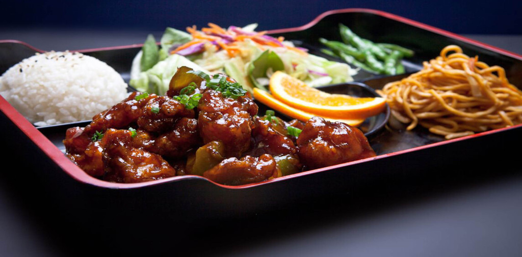 A Bento box is served with a meat entree, white rice, lo mein noodles, string beans, and a ginger salad.