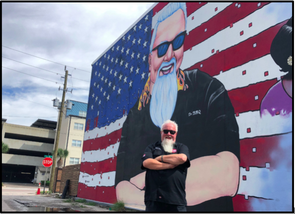 """Ray """"Dr. BBQ"""" Lampe standing in front of the Dr. BBQ mural by Cam Parker (aka Painkiller Cam)"""