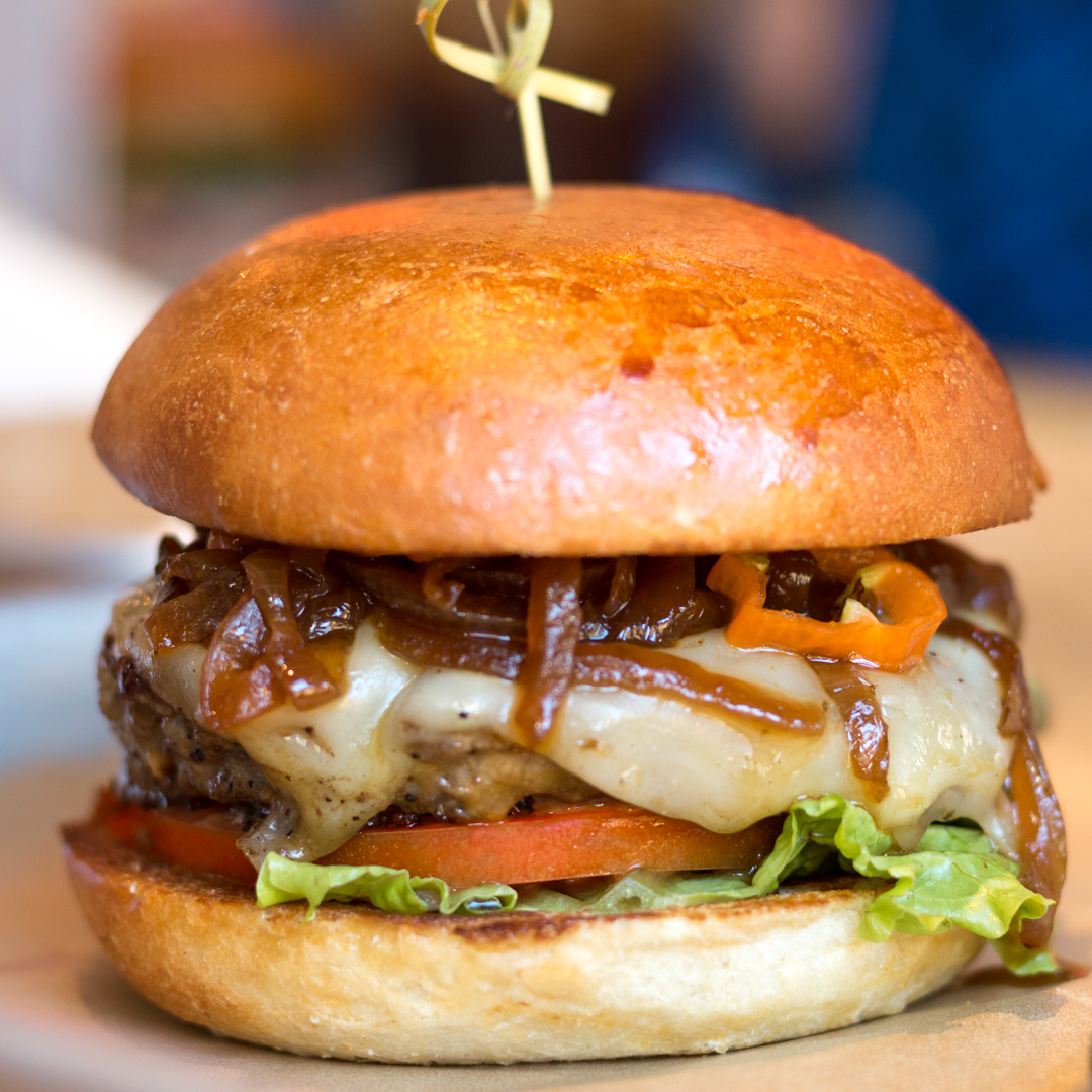 El Diablo, an angus beef burger topped with Tillamook pepper jack, habañeros, serranos, caramelized onions, salsa roja, chipotle aioli, lettuce, and tomato.