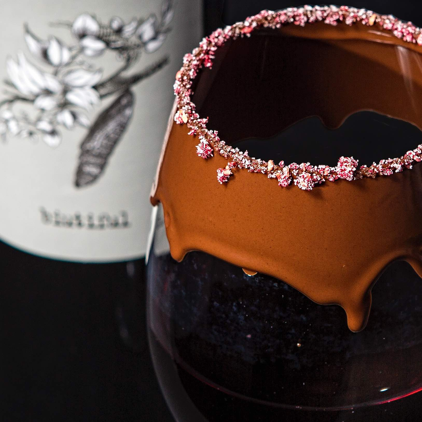 Berry Naughty - Malbec in a Semi-Sweet Chocolate Rimmed Wine Glass. Topped with Raspberry Sugar.