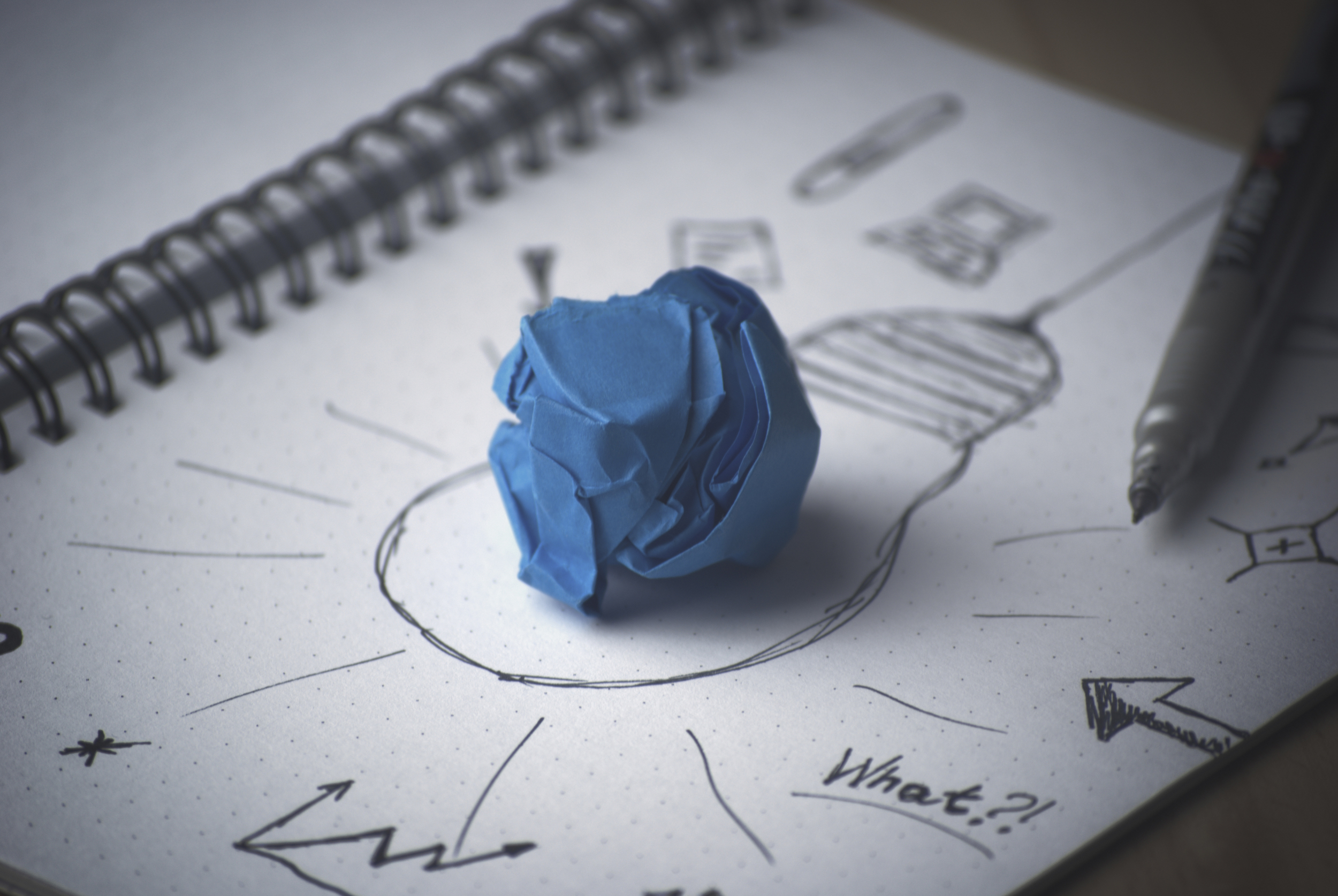 Crumpled paper ball on drawing of lightbulb