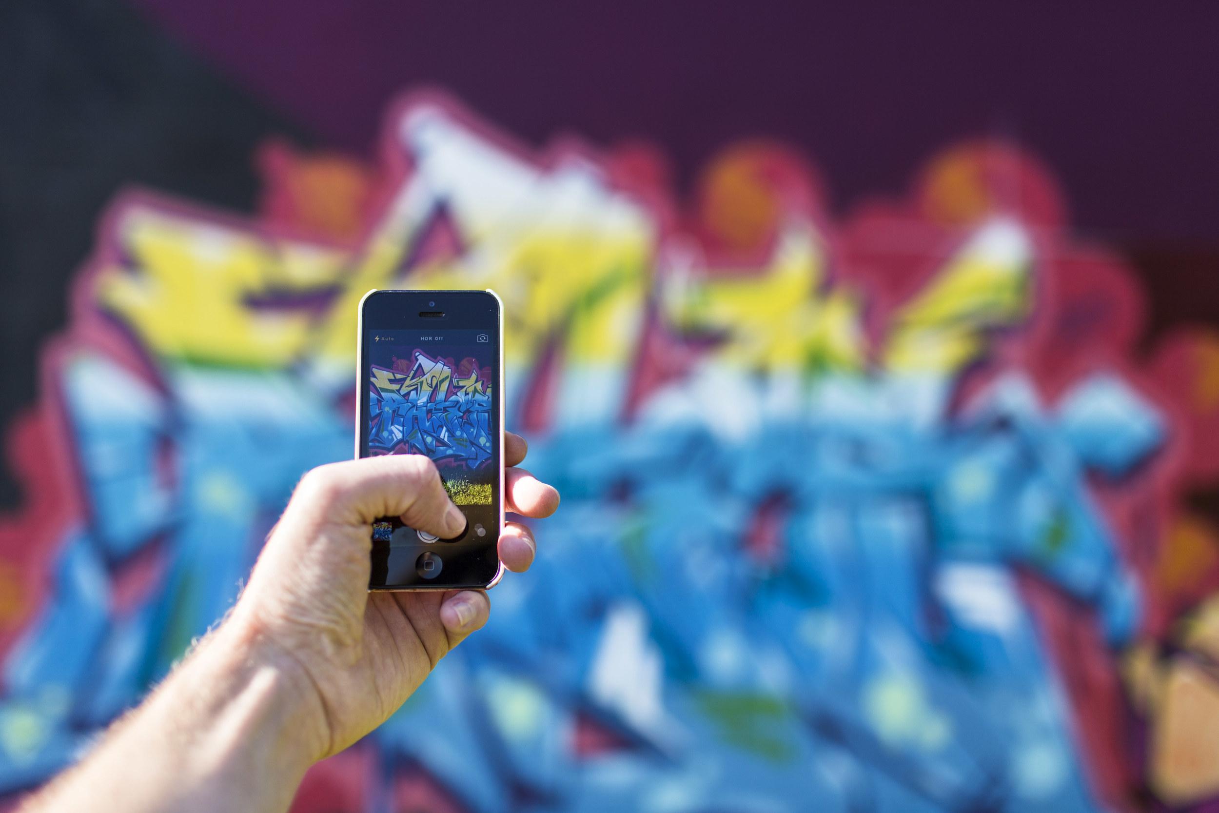 Smartphone taking photo of graffiti