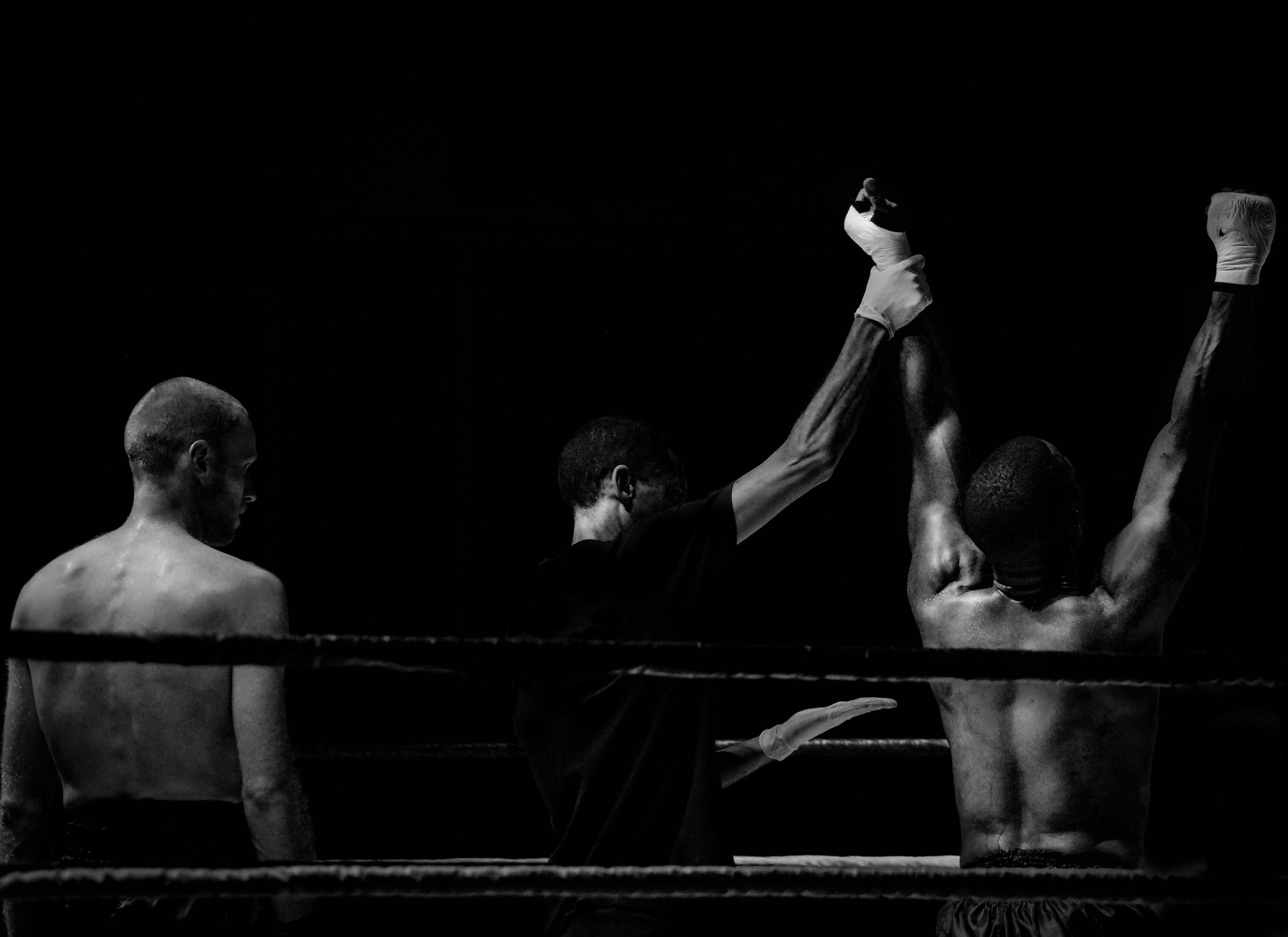 Victorious boxer having his arm raised