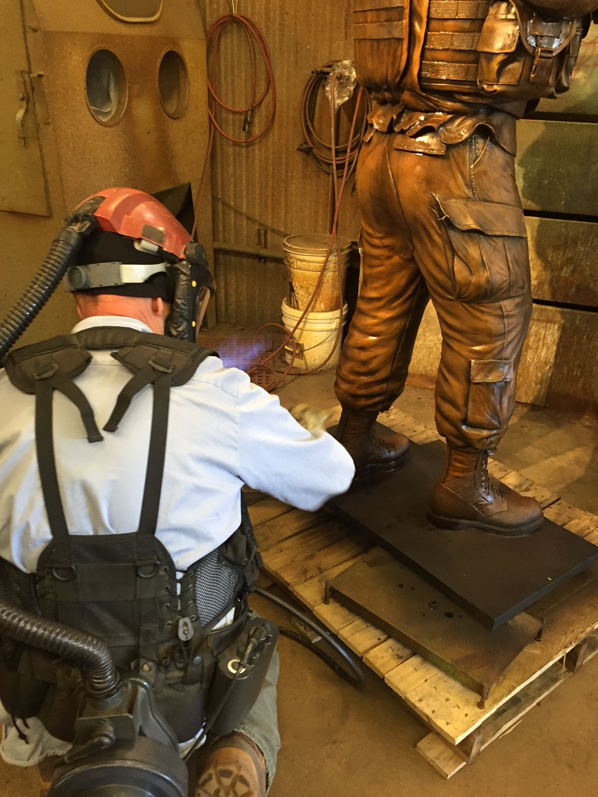 Patina Artist Nate Ford applying a hot wax finish to seal the patina.