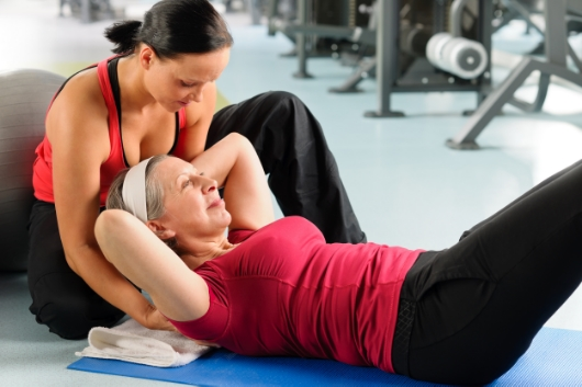 12758353-Fitness-center-senior-woman-exercise-sit-ups-with-personal-trainer-Stock-Photo.jpg