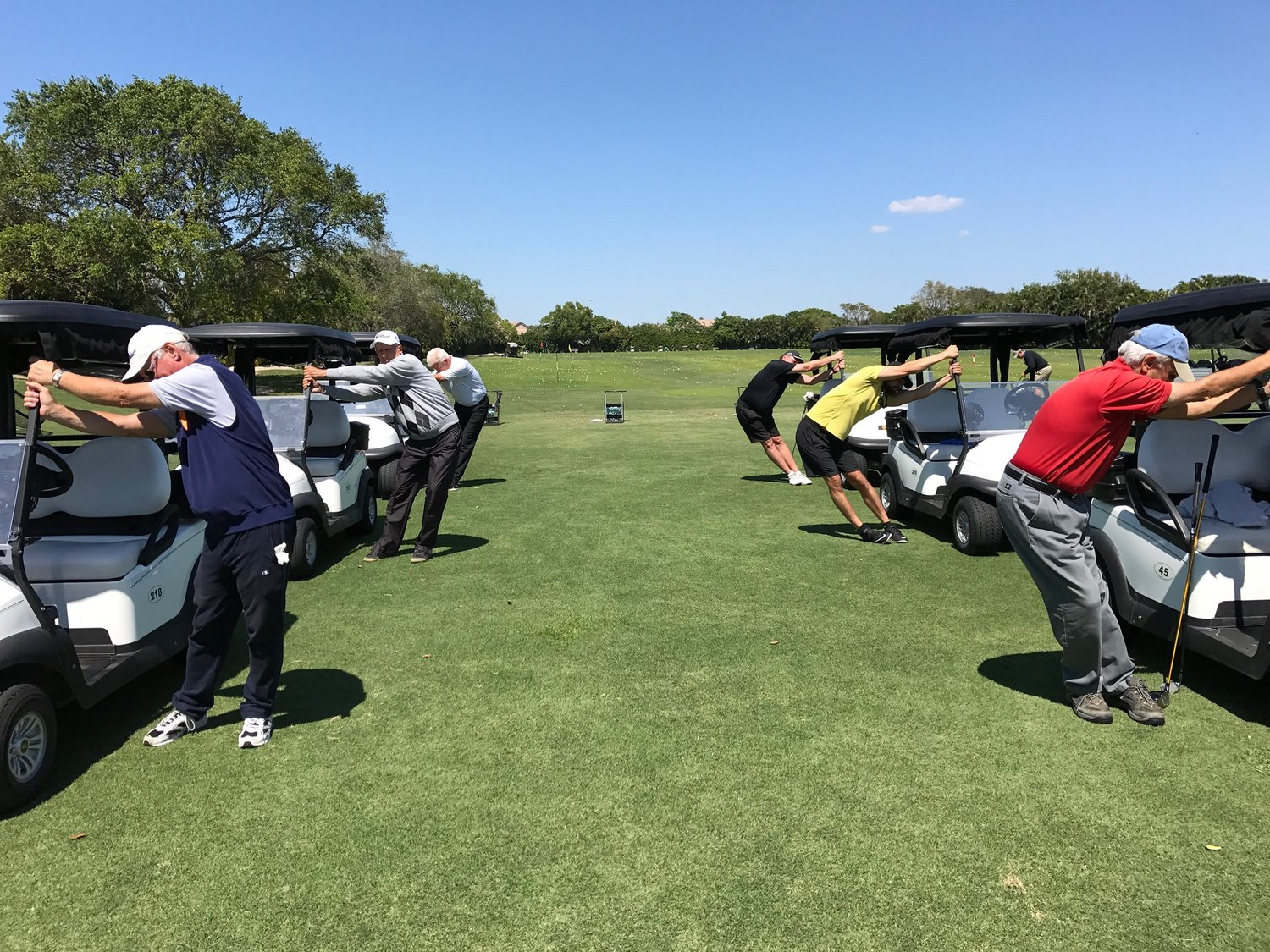 MEMBERS AT A LOCAL COUNTRY CLUB DEMONSTRATING GOLF STRETCHES FROM THEIR GOLF CARTS