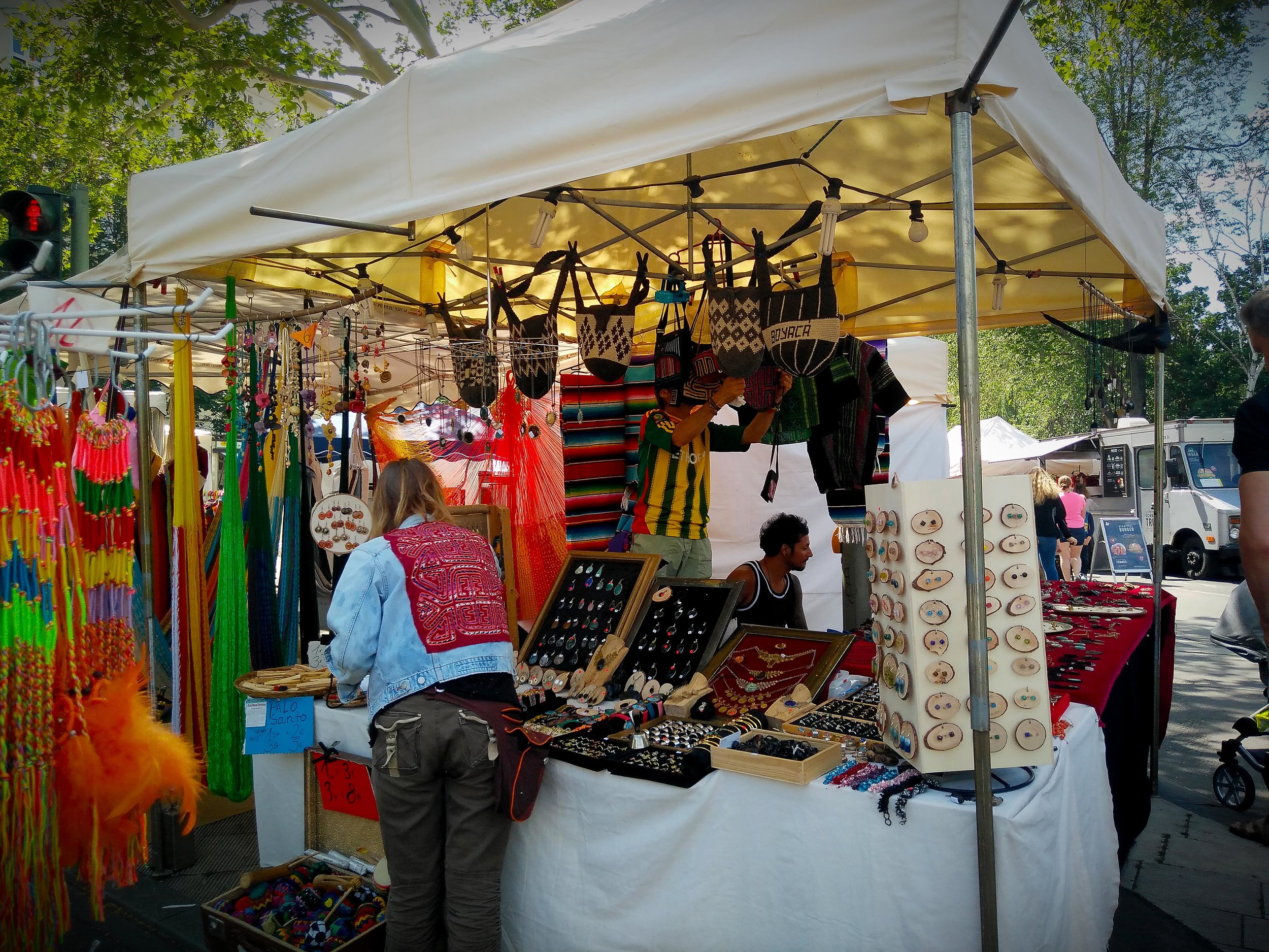 Carnival of Cultures, Berlin, Germany 2019. Vendor selling hand braided bracelets, trinkets, necklaces, and other accessories. The jean sweater has a mola textile attached on the back.