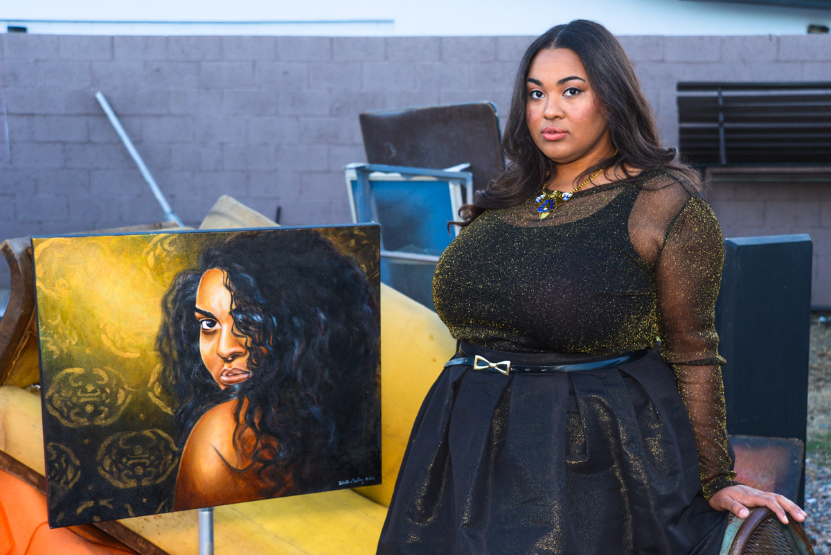 """Artist Antoinette Cauley pictured with her painting titled """"Love Can Make A Bitch Go Crazy"""". Photo by Dontae Tubbs/ Hair by Annie Cavnaugh/ Makeup by Stephanie Hernandez"""