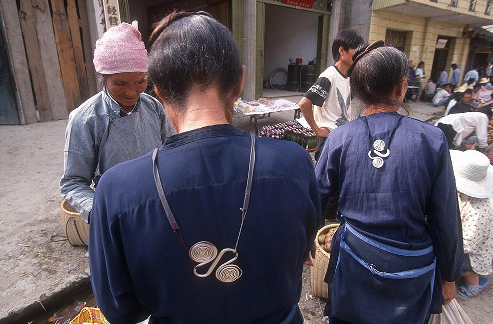 Mulheres  Dong  com roupas tradicionais tingidas de índigo. As peças em prata que se veem nas suas costas são utilizadas como contra-peso para uma espécie de avental.
