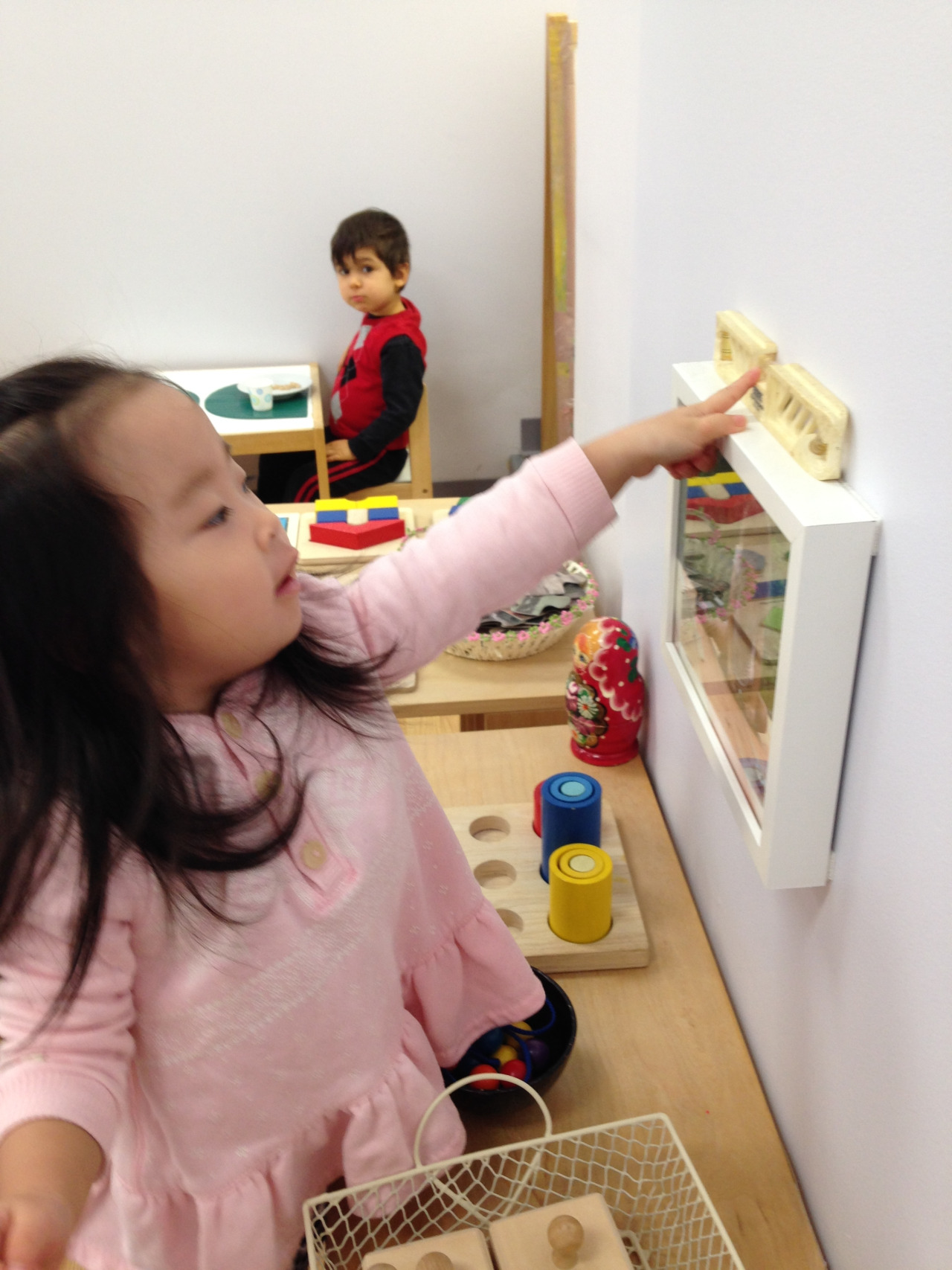 Recently, a level was discovered on the shelf in the Toddler 1 classroom. Many students enjoy sitting peacefully watching the bubble go back and forth, while a few were determined to learn how to use it. One Toddler went around to each of the classroom photographs, step stool in tow, carefully examining the tiny bubble to test how level the artwork was hanging!