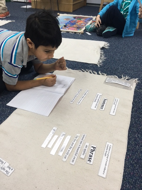 A first grade Lower Elementary West student worked on his Language follow up, differentiating between phrases and sentences.