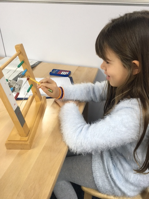First grade Lower Elementary West students received a lesson about using the Small Bead Frame to work on their addition and subtraction skills.  This work offers a step toward abstraction and the material is another option to work on their skills.