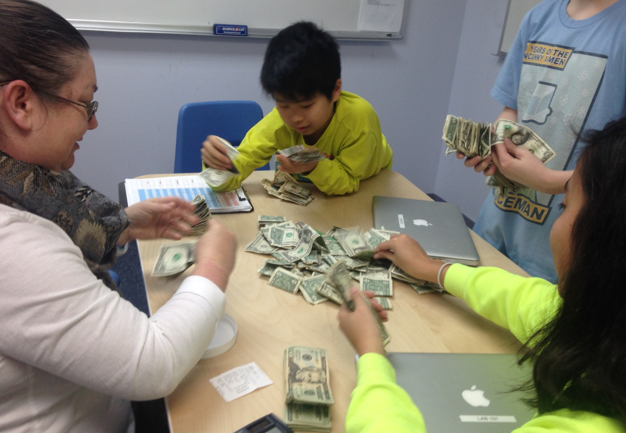 As they prepare for the upcoming Montessori Model UN, the Middle School students and Ms. Sarah counted money from fundraising projects.