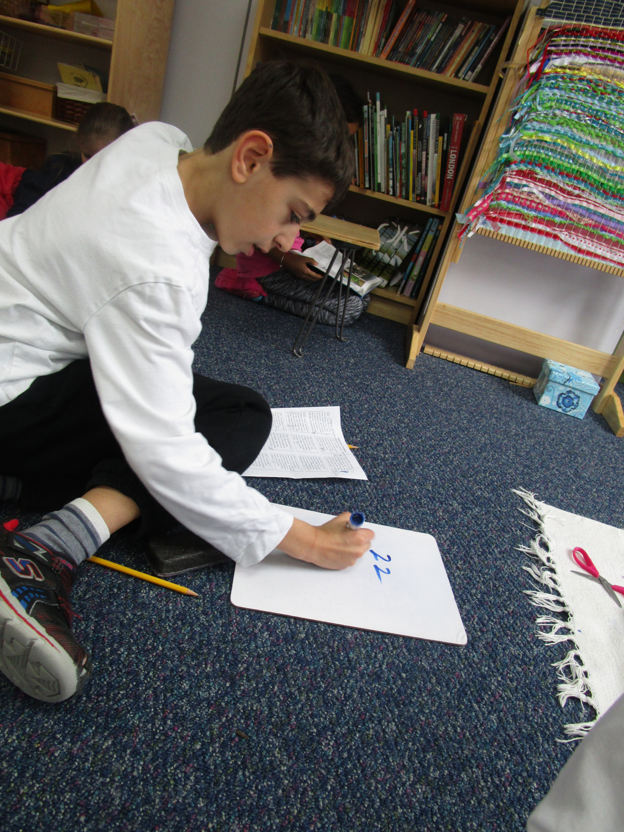 A Lower Elementary North student used a small white board to work out multi-step word problems.