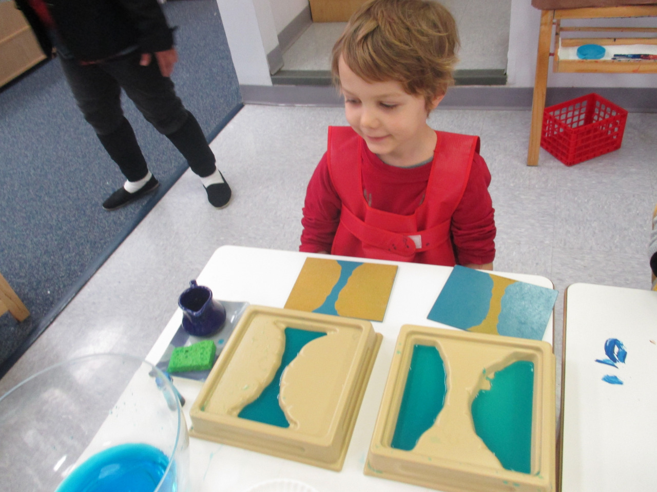 As a part of their study of land and water forms, the Primary 1 Kindergartners took a closer look at 'strait' and 'isthmus'. They poured water into the strait and isthmus trays and also used modeling clay on a paper plate to recreate these two land and water forms.