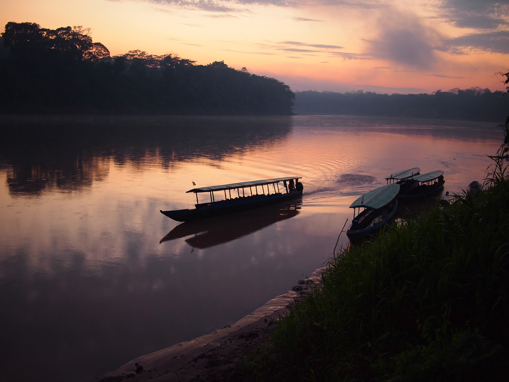 Boat navigating the Tambopata river during sunrise in the Peruvian jungle