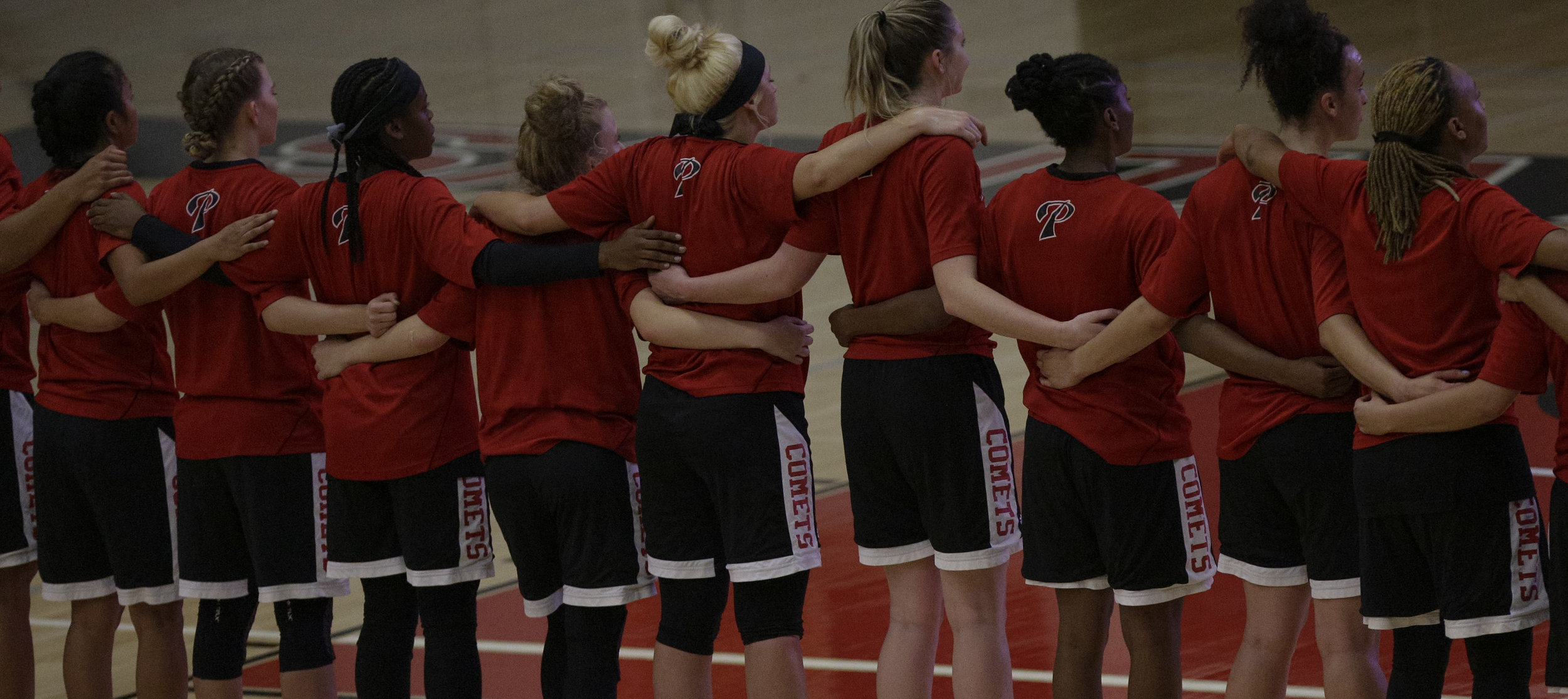 The Palomar Comets womens basketball team in arms around eachother during the national anthem before facing off against The Santa Ana College Dons . The Dons would fall to the Comets 76-61.   Photo taken October 3rd 2016 at Santa Ana College in Santa Ana Calif..         Photo By: Daniel Bowyer/Sports Shooter Academy