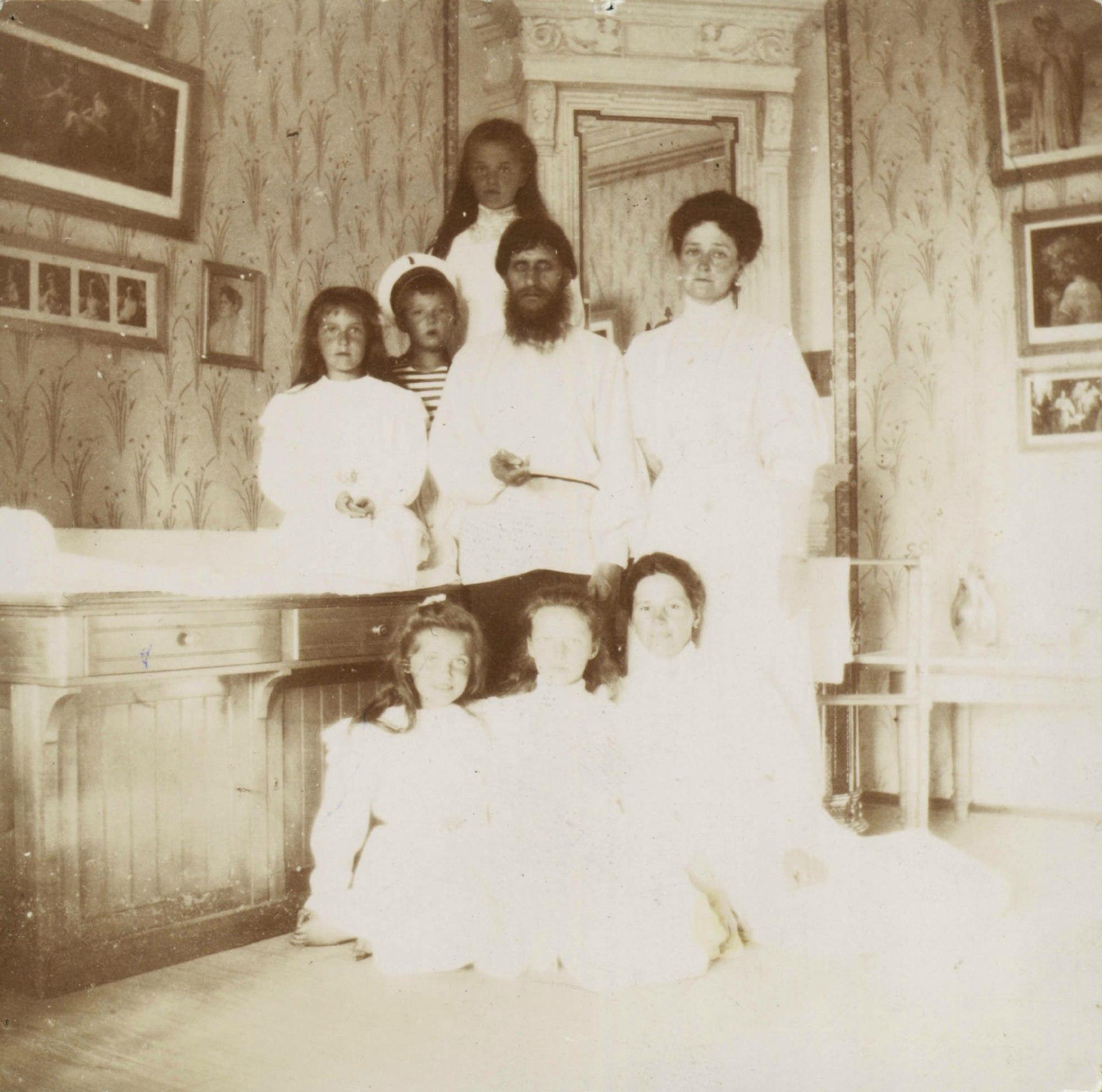 1920px-Alexandra_Feodorovna_with_Rasputin,_her_children_and_a_governess.jpg