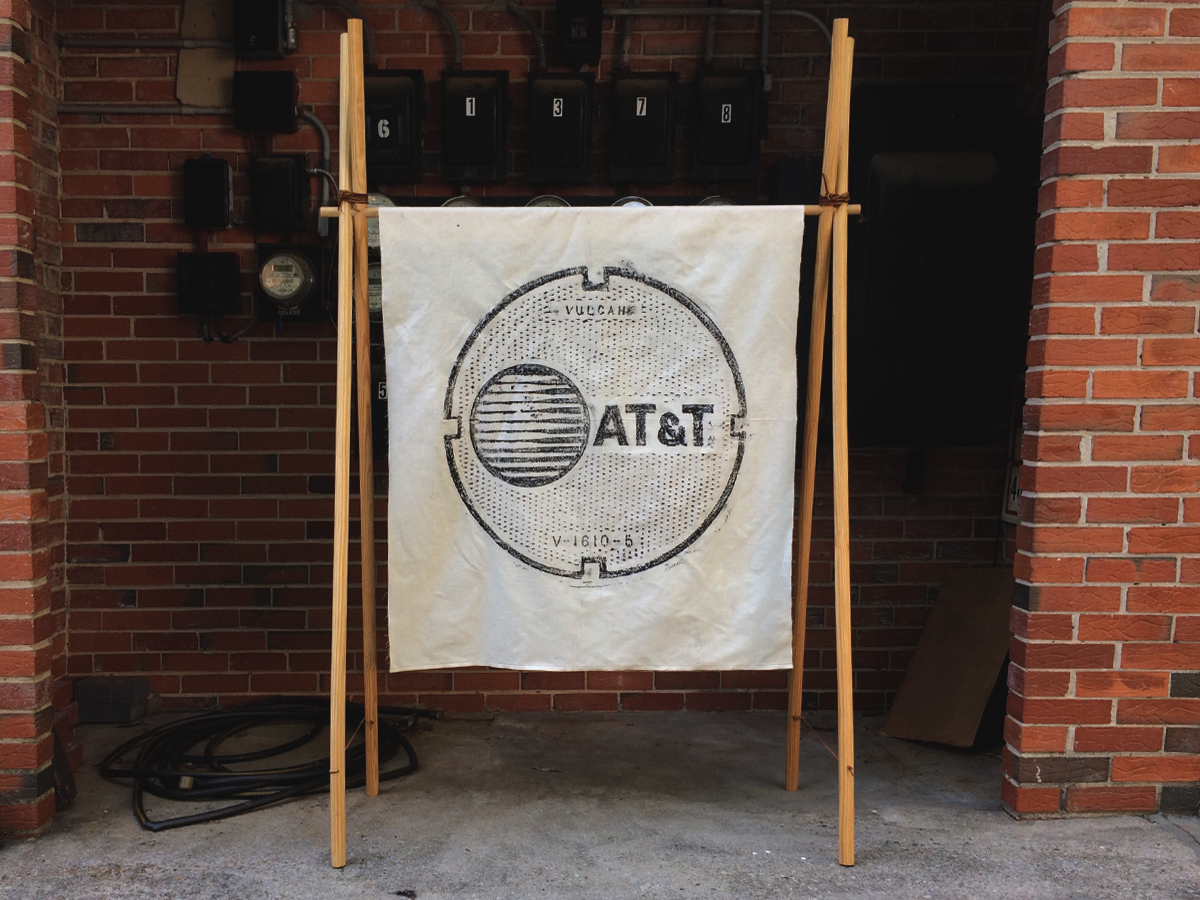 """AT&T  - Size 37.6""""x45"""" (100% Cotton) - Wax Rubbing of a manhole cover - Print size 28""""x28"""" - Three 1/2"""" gold metal grommets"""