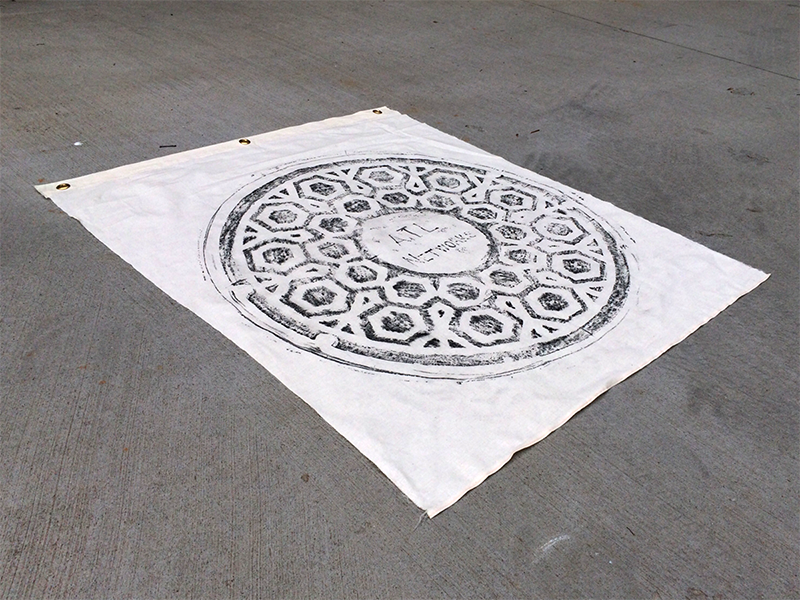 """ATL NETWORKS   - Size 38""""x45"""" (100% Cotton) - Wax Rubbing of a manhole cover - Print size 35""""x34"""" - Three 1/2"""" gold metal grommets"""