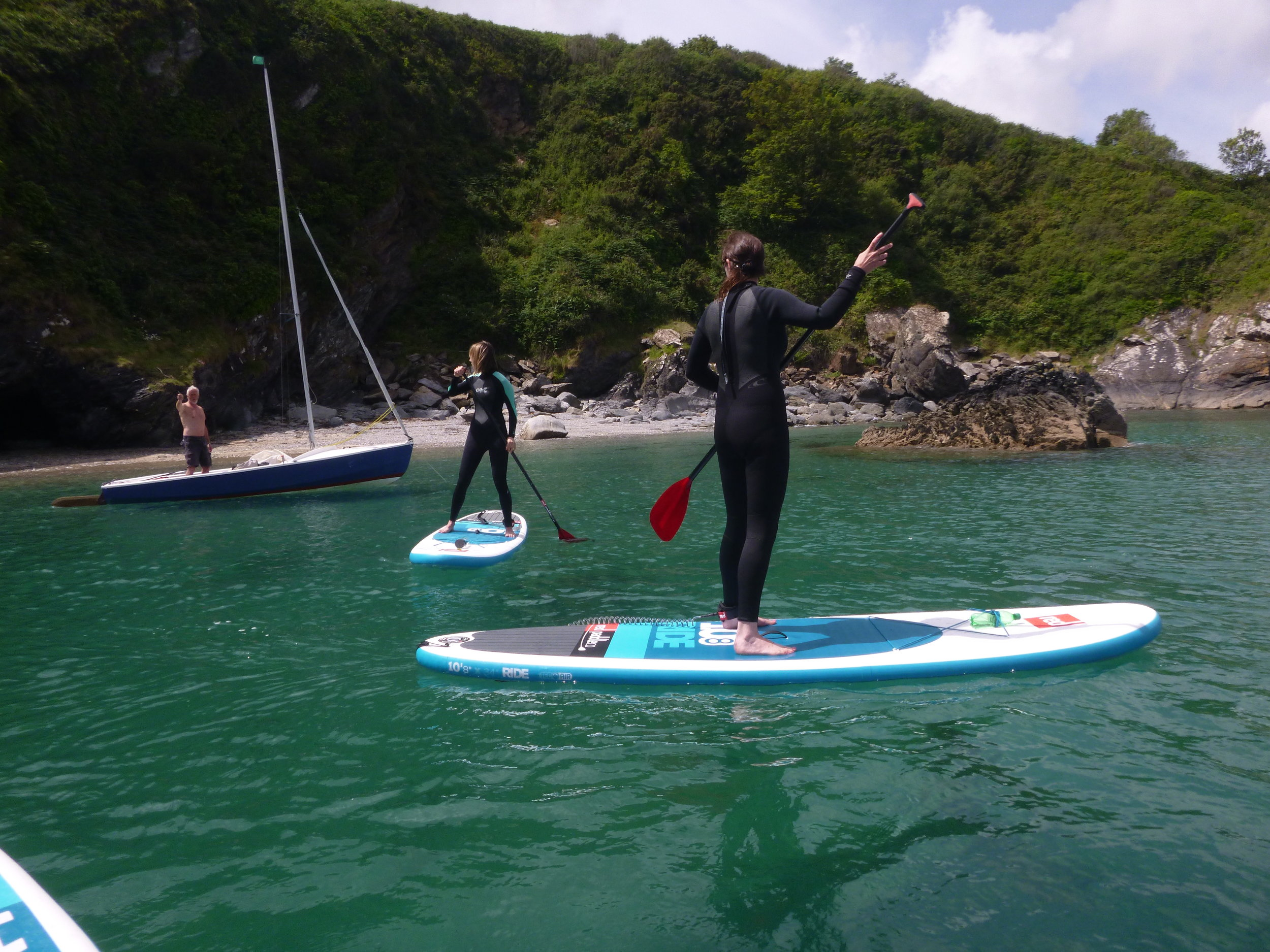 Chatting to the locals. Clear waters and stunning views paddle boarding from Maenporth one of the family friendly Falmouth beaches.