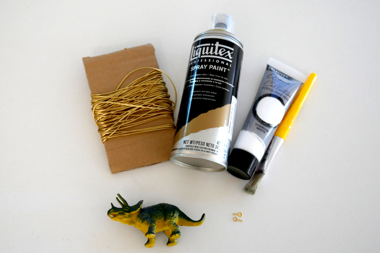 The materials we used: cheap plastic dinosaurs, small screw hooks, white paint, gold spray paint and gold string.