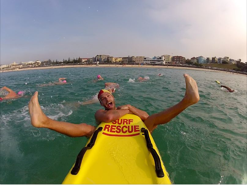Just another day in the office for @northbondislsc training officer Justin. The crew at North Bondi train approx 100 new lifesavers each year, and everyone does this voluntarily! You can spot the new Bronzies wearing the pink caps, which they will exchange for red and yellow caps when they graduate. Pic: Ben McCormack.