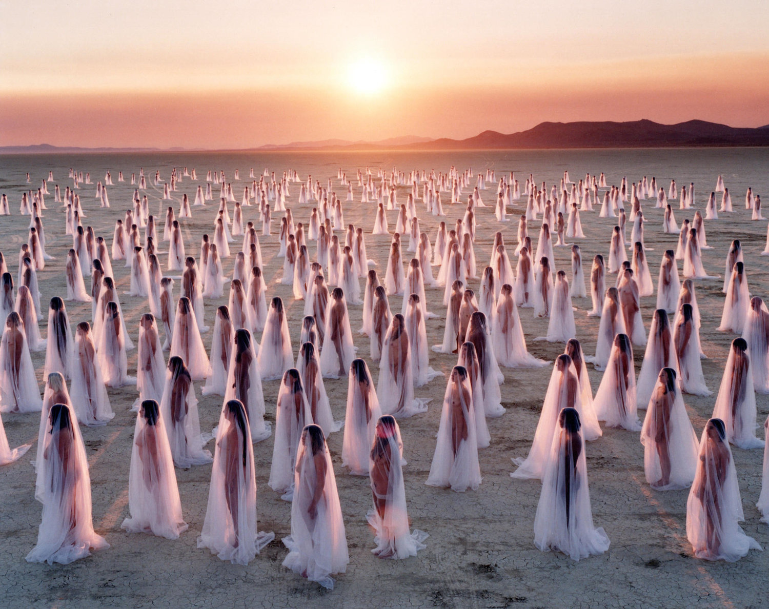 Over a career spanning more than 25 years, Tunick has staged 125 mass nude installations in 25 countries, photographing tens of thousands of volunteers in their birthday suits. He has been arrested for it five times.  Critics say he's a one-trick pony chasing publicity; fans say his work transcends difference and foregrounds the humanity in our industrialised lives.  Either way his popularity is undeniable, with those who model for him saying it's liberating and unforgettable. None of them gets paid but everyone receives a print of the photograph in which they appear.