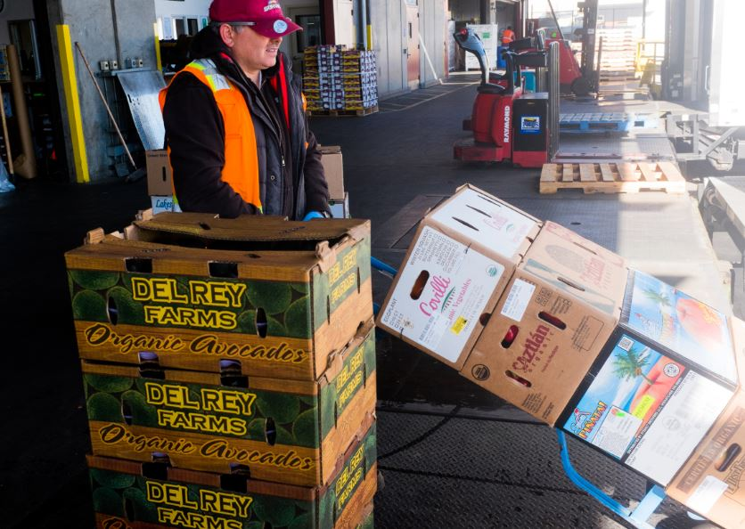 A worker unloads organic produce from the Central Valley at a food distribution center in SF