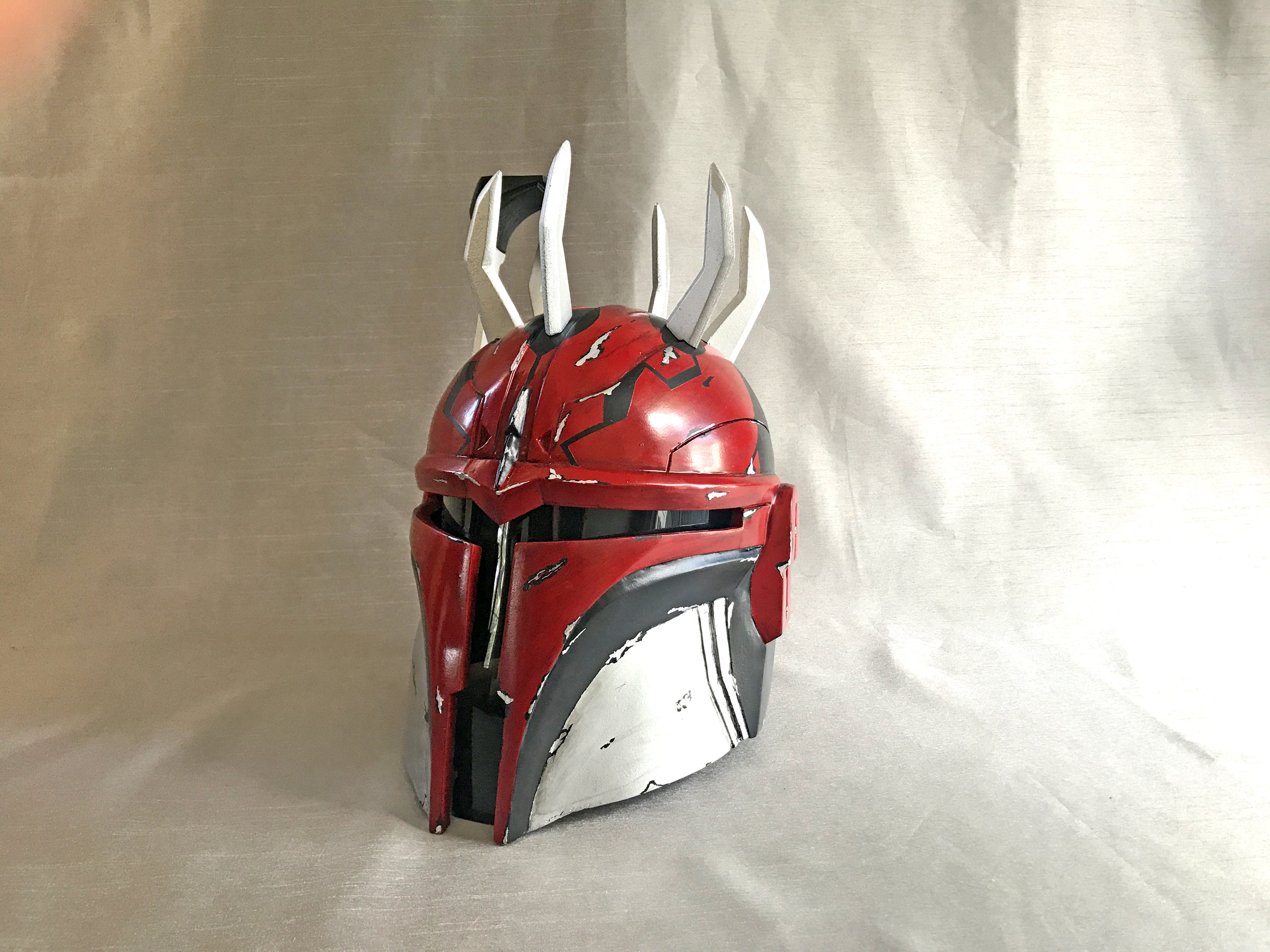Contacted by a client who loved our Variant style helmet, we were asked to create a stunning piece inspired by Darth Maul. To approach something like this we took our basic Variant helmet and prepared it for painting. After priming the helmet we were ready to paint.  There is no template for a project like this. With Darth Maul reference photos we began to mask off the helmet appropriately while also planning to paint the damage.  Once finished we drilled out holes for the horns to be set. We threaded the horns to accept screws from the underside. The visor was then set and screwed in to provide a removable lens. Five helmet squares were added and the project was marked as complete.