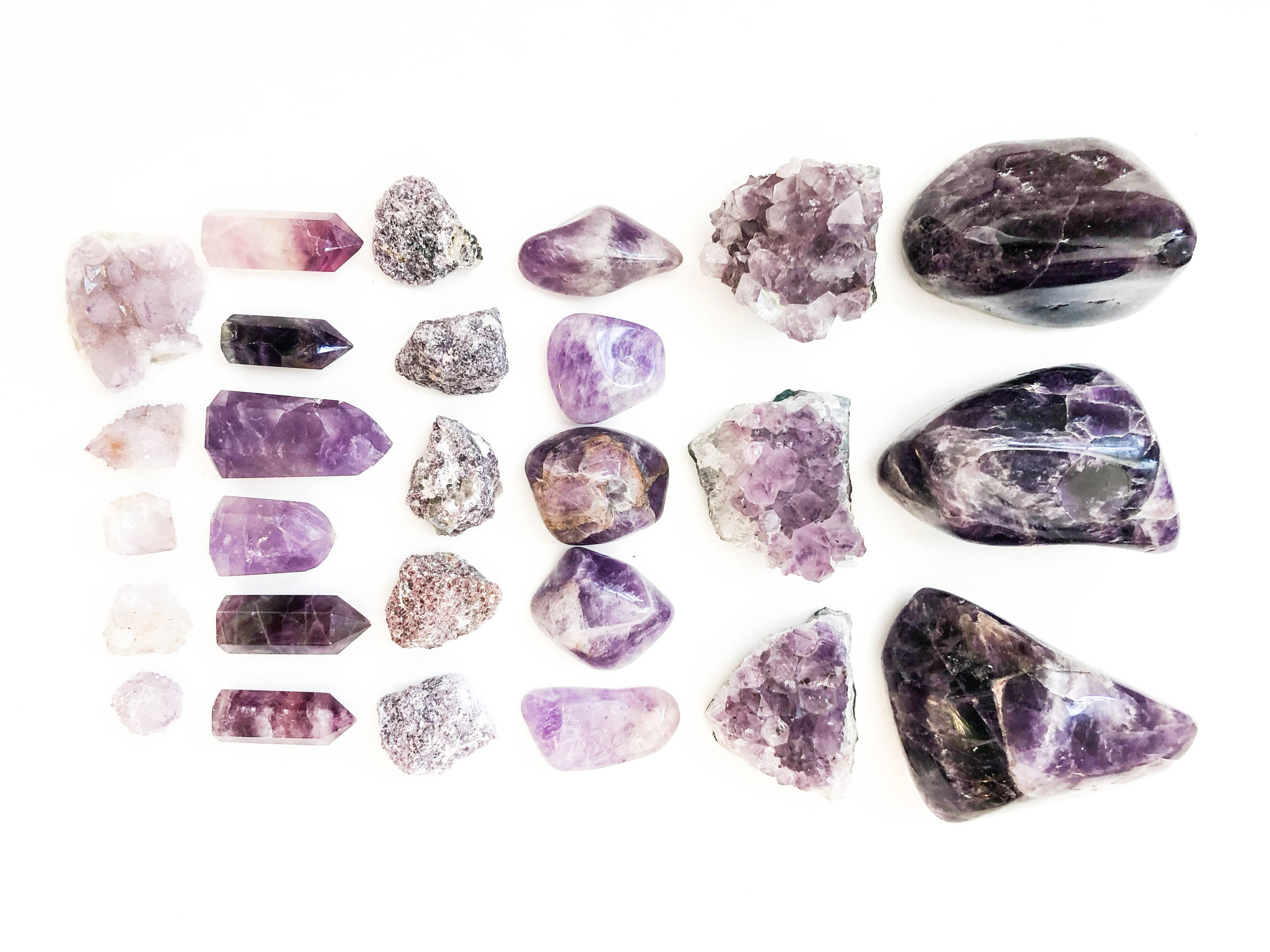 Left to Right: Spirit Quartz Clusters, Fluorite Amethyst Points, Lepidolite, Amethyst Tumbled, Amethyst Cluster, Large Chevron Amethyst Chunks.  Amethyst enhances intuition and dreams. Lepidolite has lithium in it and is good for anxiety. Spirit quartz is for divine spirituality.