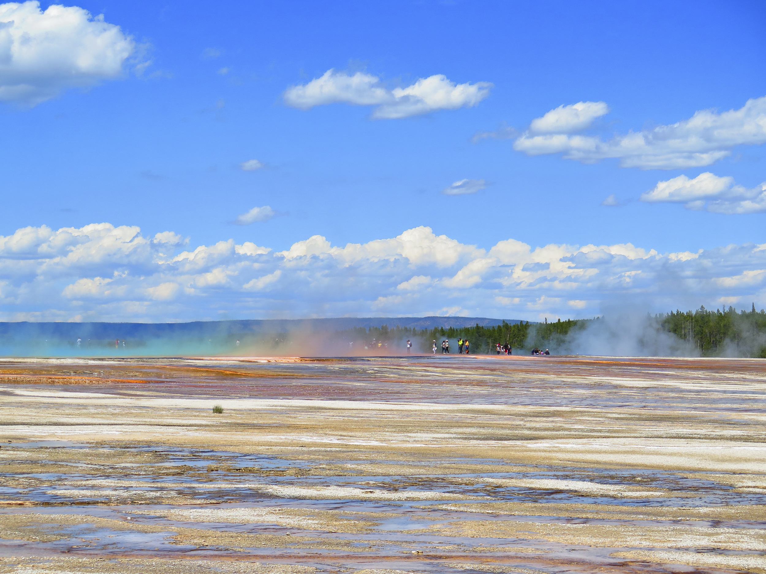People walking through the steam coming out of the Grand Prismatic Spring.