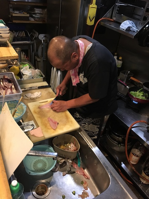 The scene on the other side of the counter of a lively izakaya in Hiroshima