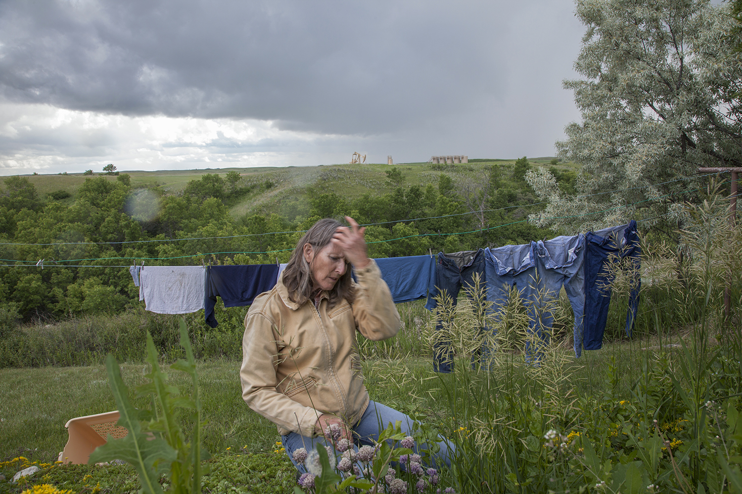 Brenda Jorgenson, whose family does not own underlying mineral rights, is distressed by the presence of oil wells on theirland  Tioga, ND. 2012