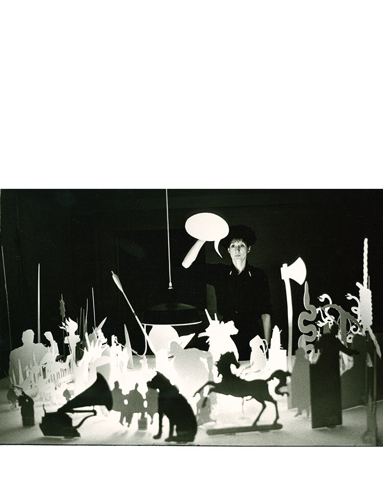 Rose Finn-Kelcey   Glory  1983 Card, metal, wood, speakers, sound system, acrylic, arrow, red gloves (A performance involving 100 cardboard cut-out surrogate performers, croupiers shovel, other implements and sound track)