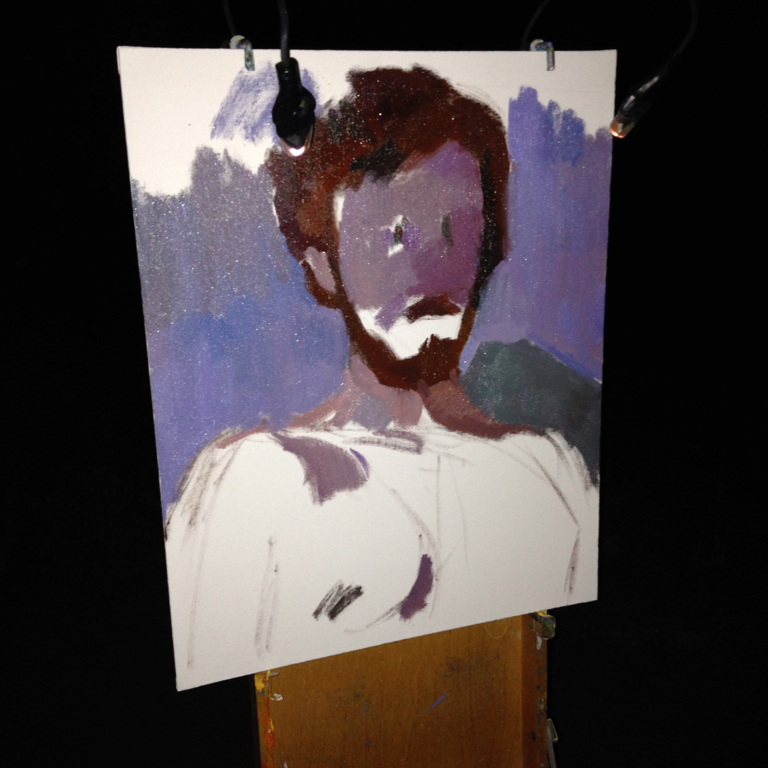 Self-portrait in progress. Color is greatly reduced at night, but we can still see some things. Two small LED lights provide enough light to see my painting and the color on the palette. Looking for big shapes and color differences at this stage.