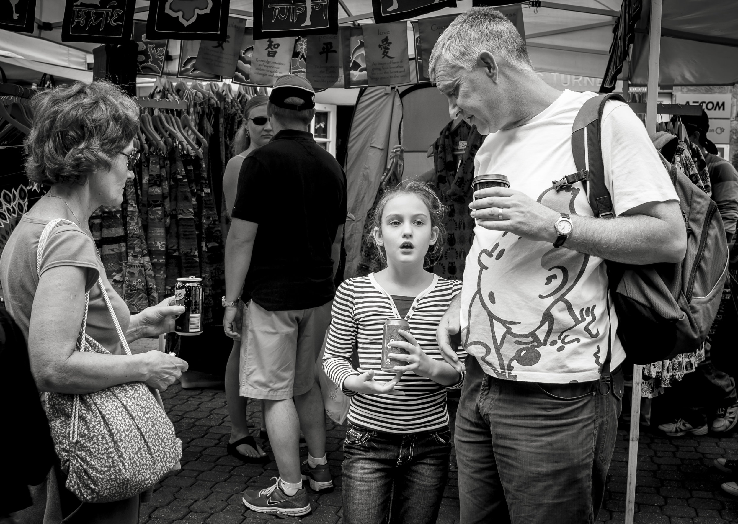 This image was captured for pleasing shape the two adults gave to the framing of the girls face, on a morning of better than normal good luck. The T-shirt, adding the extra two sets of eyes looking at the girl, making everyone look as if they are waiting for some profound decision, could not have been planned.