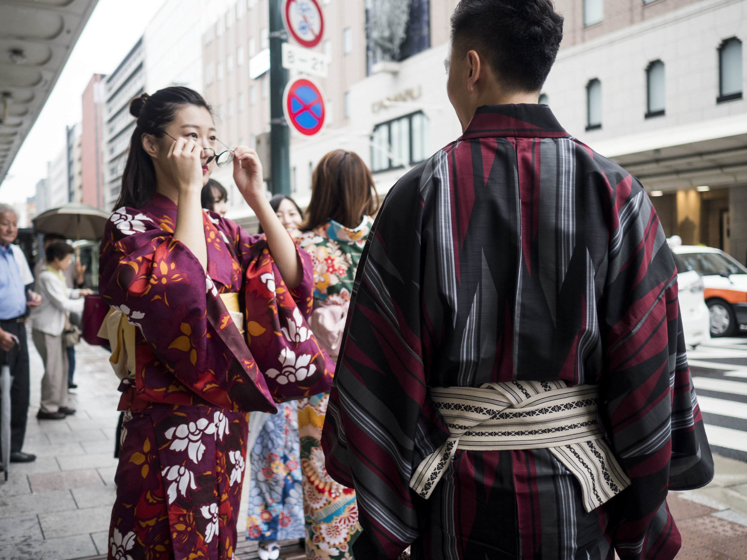 "In this image, the transition of DoF is as important as the point of perfect focus. The point of best focus is the back of the man's Kimono, but more important to the image is the woman facing us, who is not fully in or out of focus. She is caught well enough in the transition between the two. This use of transitional DoF is often referred to as ""Bokeh"" (see below) or the ""character"" of focus transition and blur and will vary by lens, aperture, distance and light."