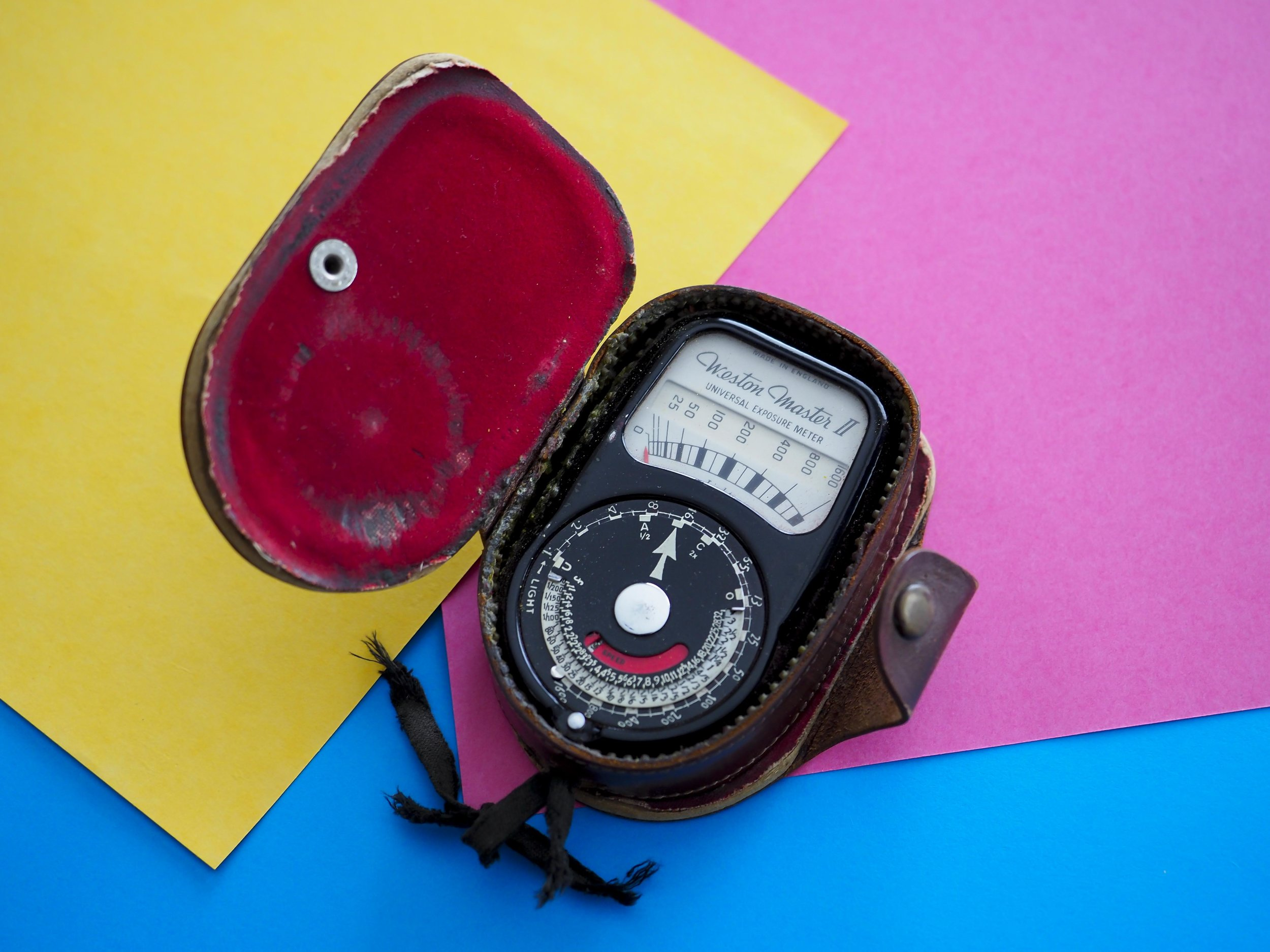 "Above is an old, but still working incident light meter and three sheets of paper that would all be roughly ""average"" tones (as is grass, tarmac, blue denim, low angle blue sky, medium brown hair etc). The light meter would be pointed towards the light source  from  the subject, giving the photographer an accurate measure of actual light falling on the subject (not reflected off of it). The paper on the other hand can be placed in open light, then a camera, reflected light meter measurement taken off of it, giving you an accurate ""average"" reading. Either way, the reading would be technically accurate. For the sake of consistency, the colour usually used is ""18%  grey"" or a grey card, but any medium tone colours have an identical effect."
